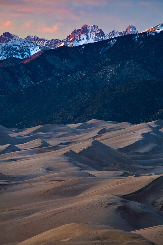 14,000 foot peaks loom over the dunes at sunset.