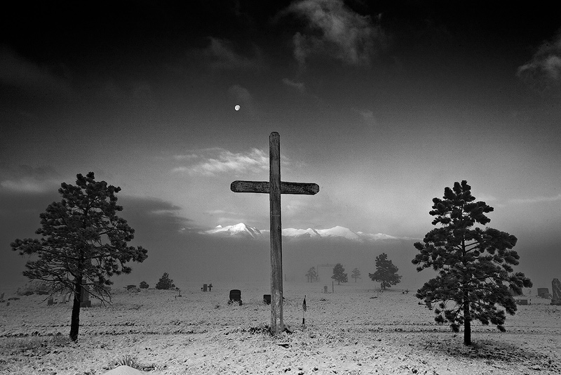 The moon sets over a cemetary in Silver Cliff, Colorado, as fog clears following a light overnight snowfall.