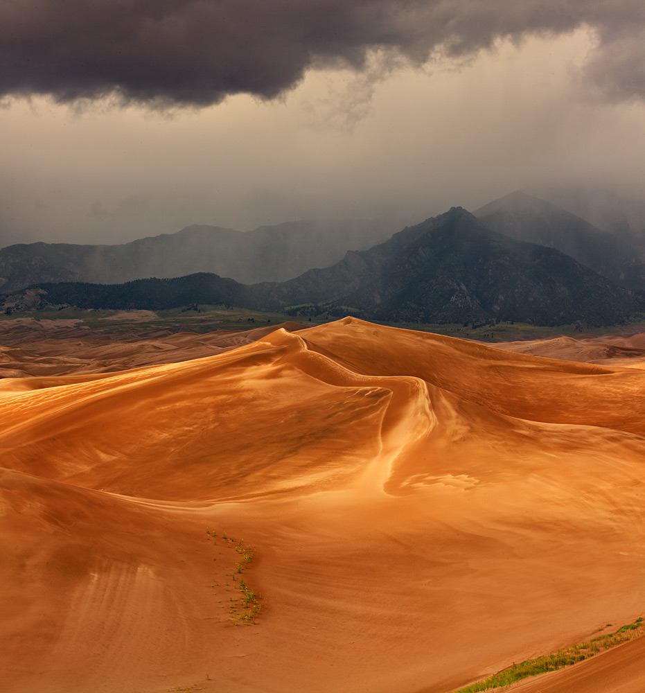 A monsoonal thunderstorm causes dramatic light in the dunes.