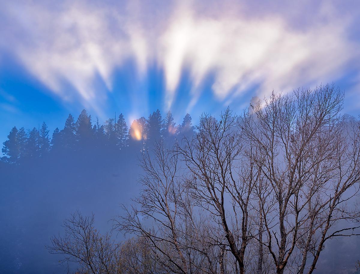 Rays of sunlight break through freezing fog over the Rampart Range in southeast Colorado