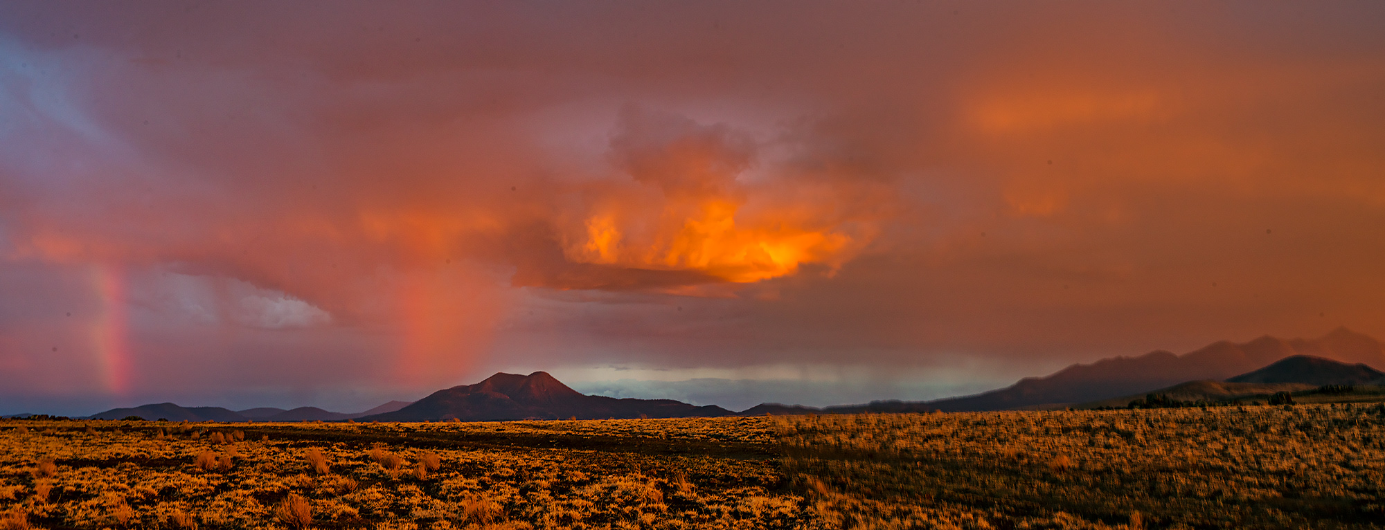 Double Rainbow and red rain over the volcanic landscape north of San Francisco Peaks.