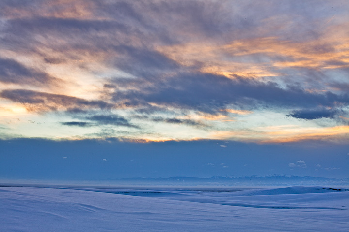 Soft pastels in January light at sunset over snow-covered dunes.