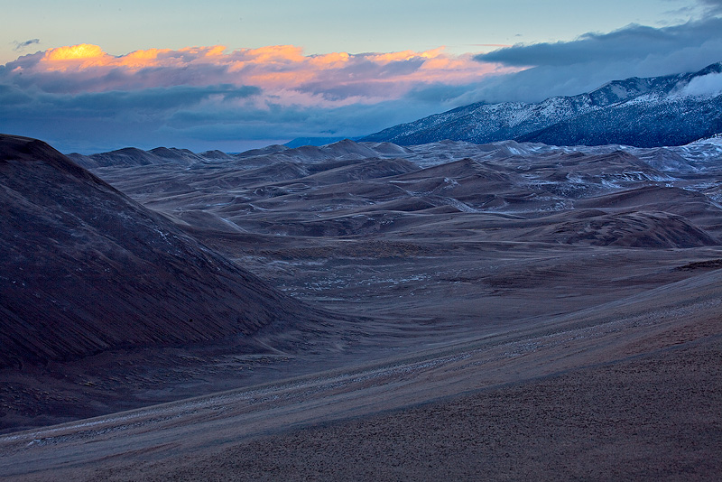 A light dusting of snow covers the dunes at sunset.