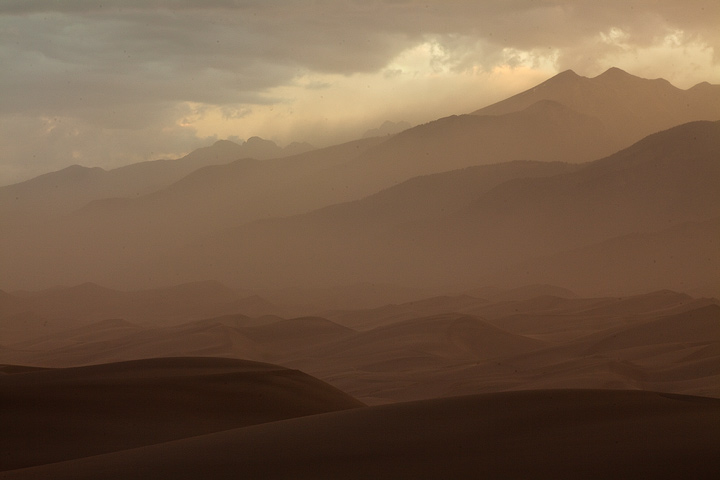 A cloud of dust and sand envelopes the Sangre De Cristo Range as the Monsoon buffets the Great Sand Dunes.