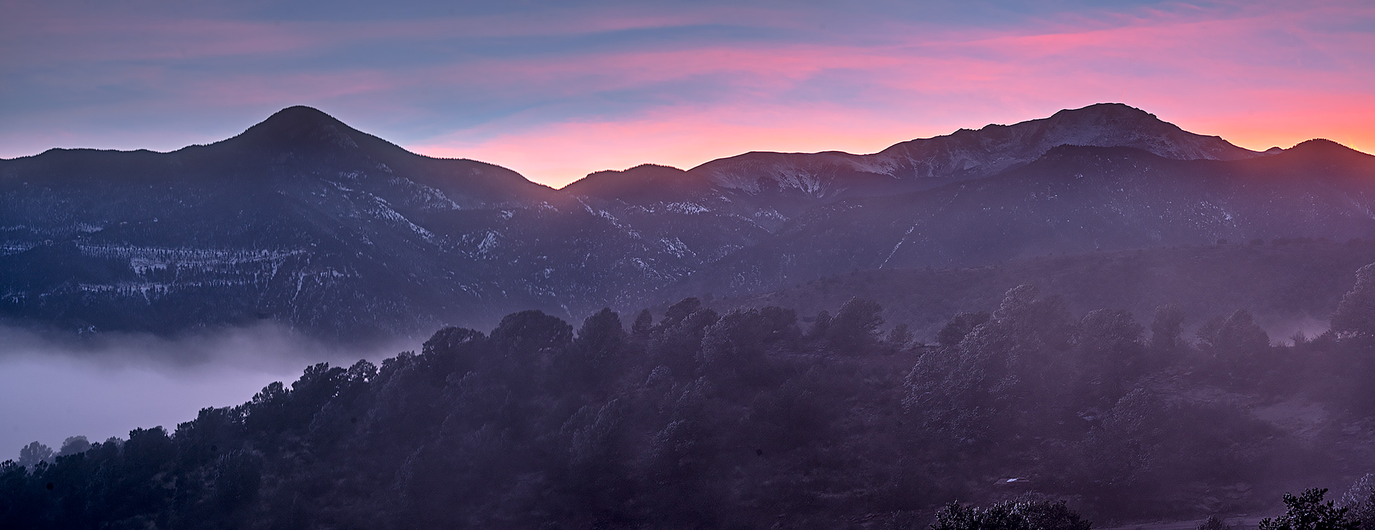 Pikes Peak and Rampart Range at sunset on a foggy frosty November day.