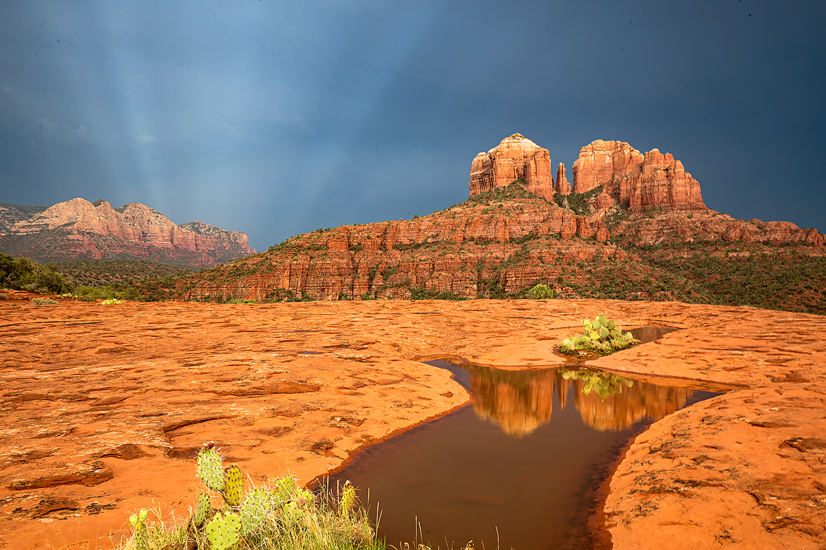 Light rays from a thunderstorm behind Cathedral Rock in Sedona.